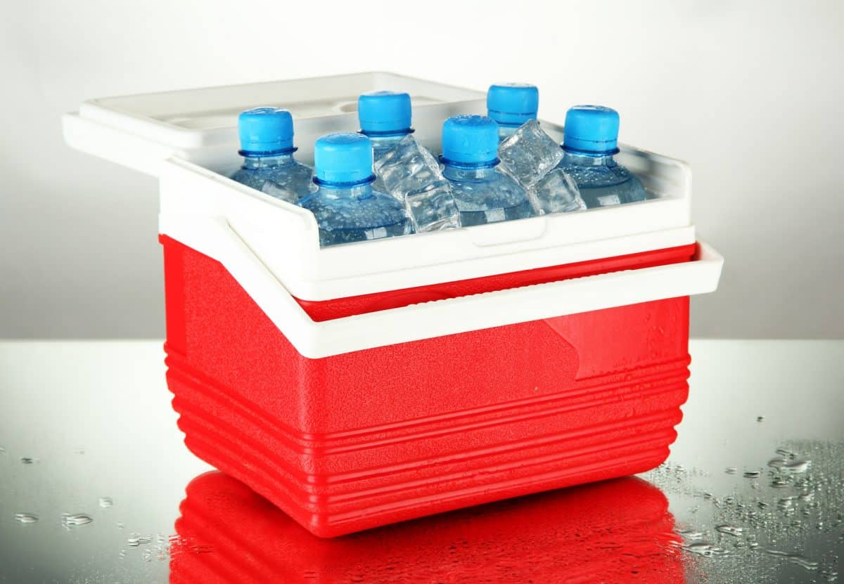 Kayak Cooler with bottles of water and ice cubes, on grey background