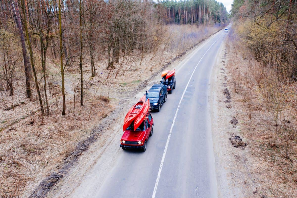 convoy of three cars carrying kayaks on their roofs