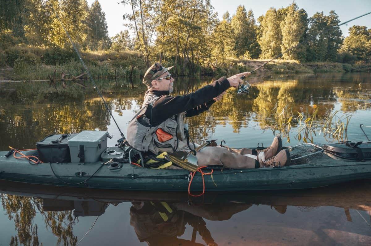 Kayak Fisherman in kayak with rod, fishing crate