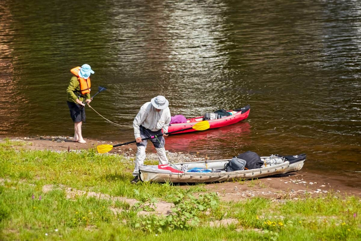 Two kayakers take a rest on the banks of a river. They are well equipped with life jackets, hats, luggage and a red and white kaja or canoe