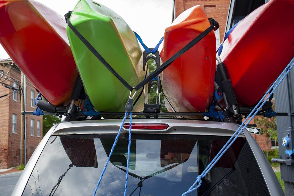 Four red and green colored full size kayaks loaded on top of an SUV car using a combination of tie down straps and roof mounted cross bars.