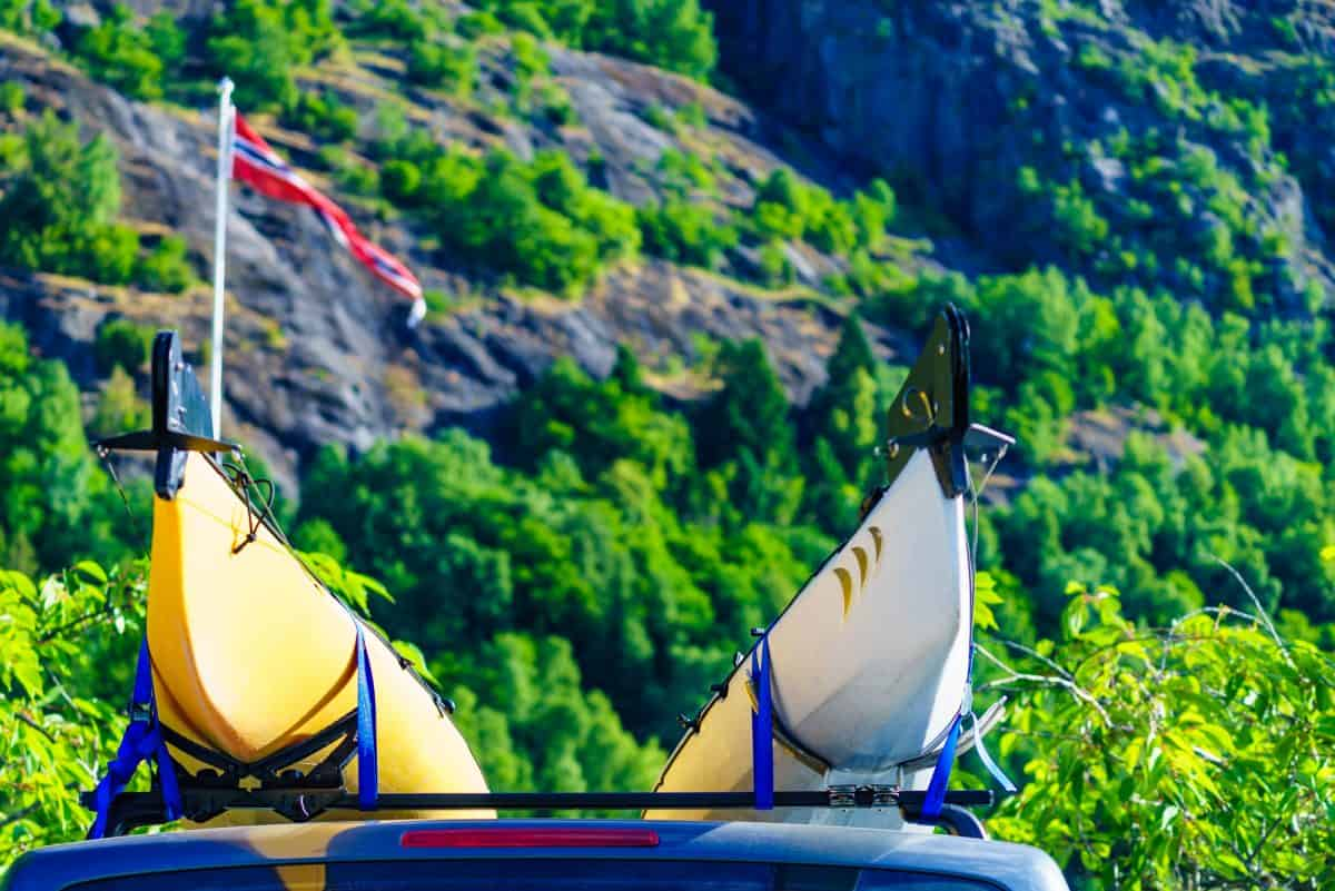 ar with two canoes on top roof in green norwegian mountains.