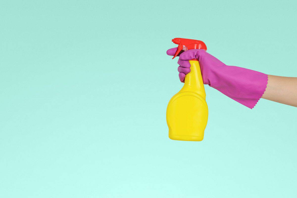 Hand in rubber glove holding a kayak wax spray bottle
