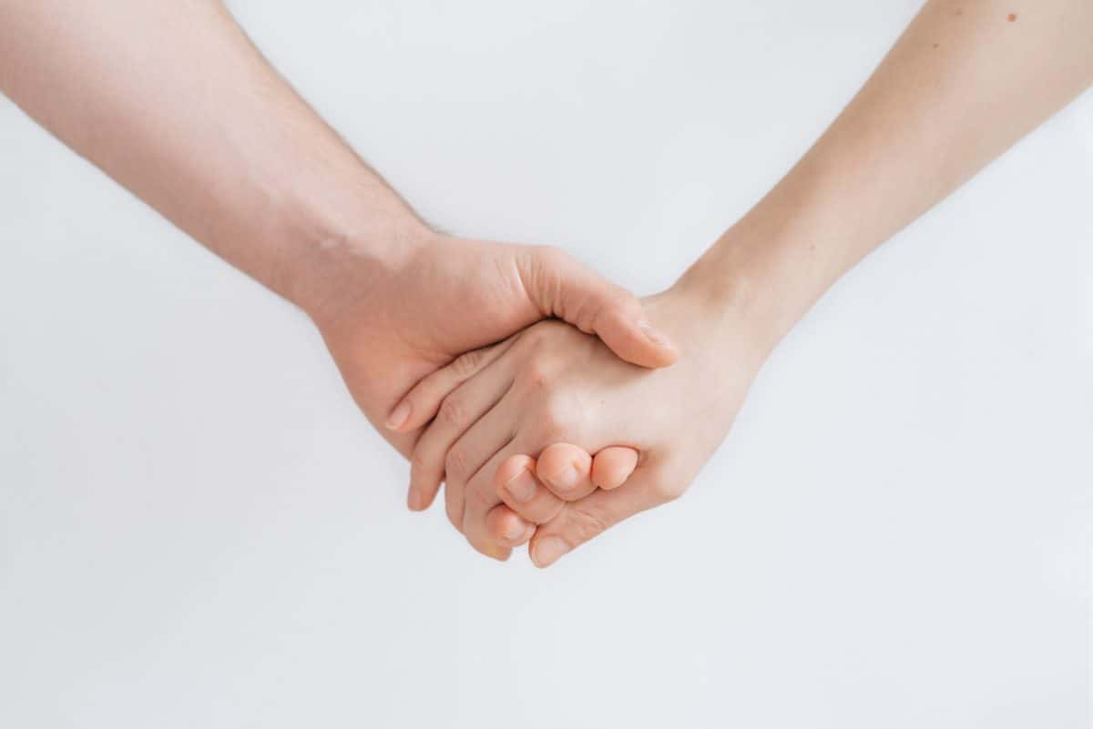 Two hands holding on white background