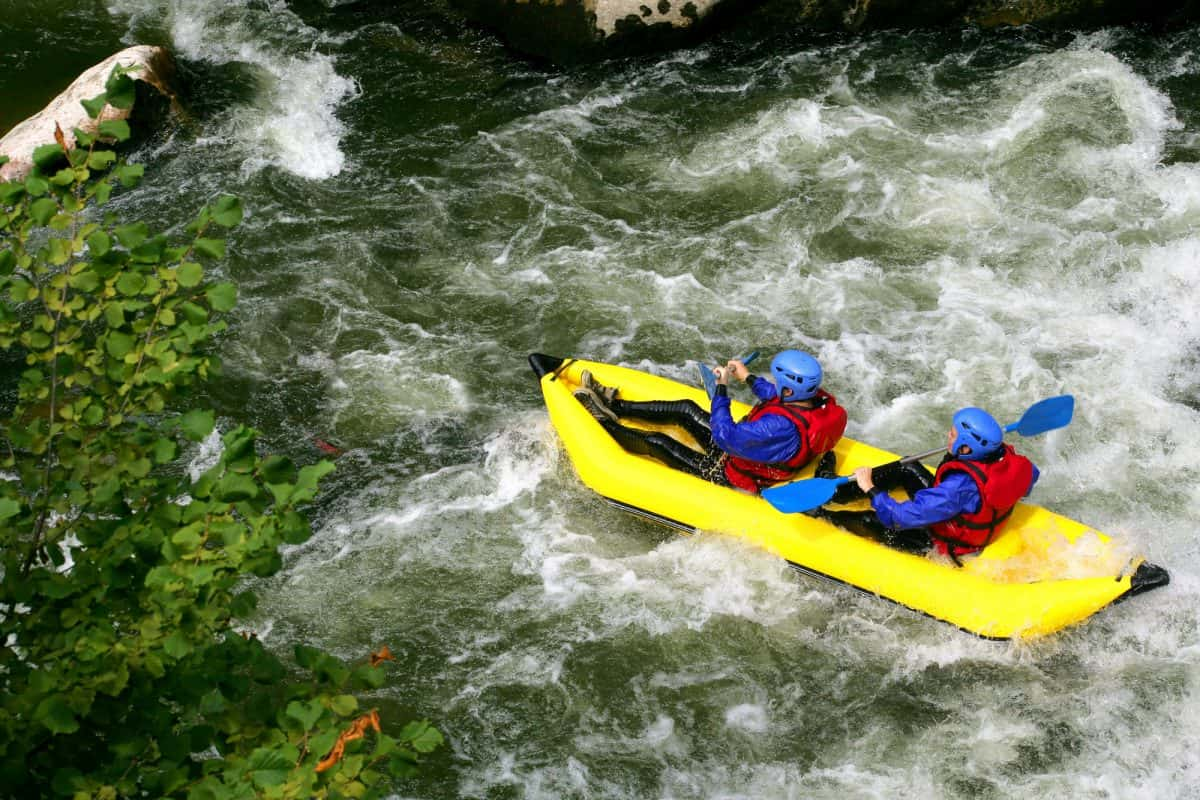 Two people kayaking down river rapids in inflatable duckie