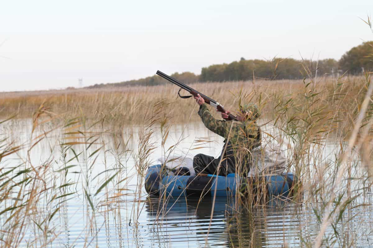 Hunter in an inflatable kayak shoots duck