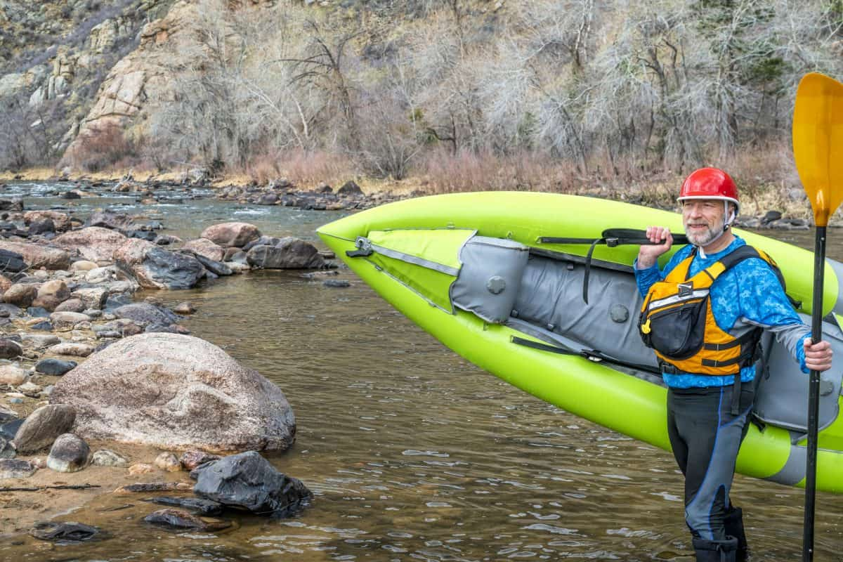 senior paddler carrying inflatable whitewater ducky kayak on a shore of mountain river in early spring