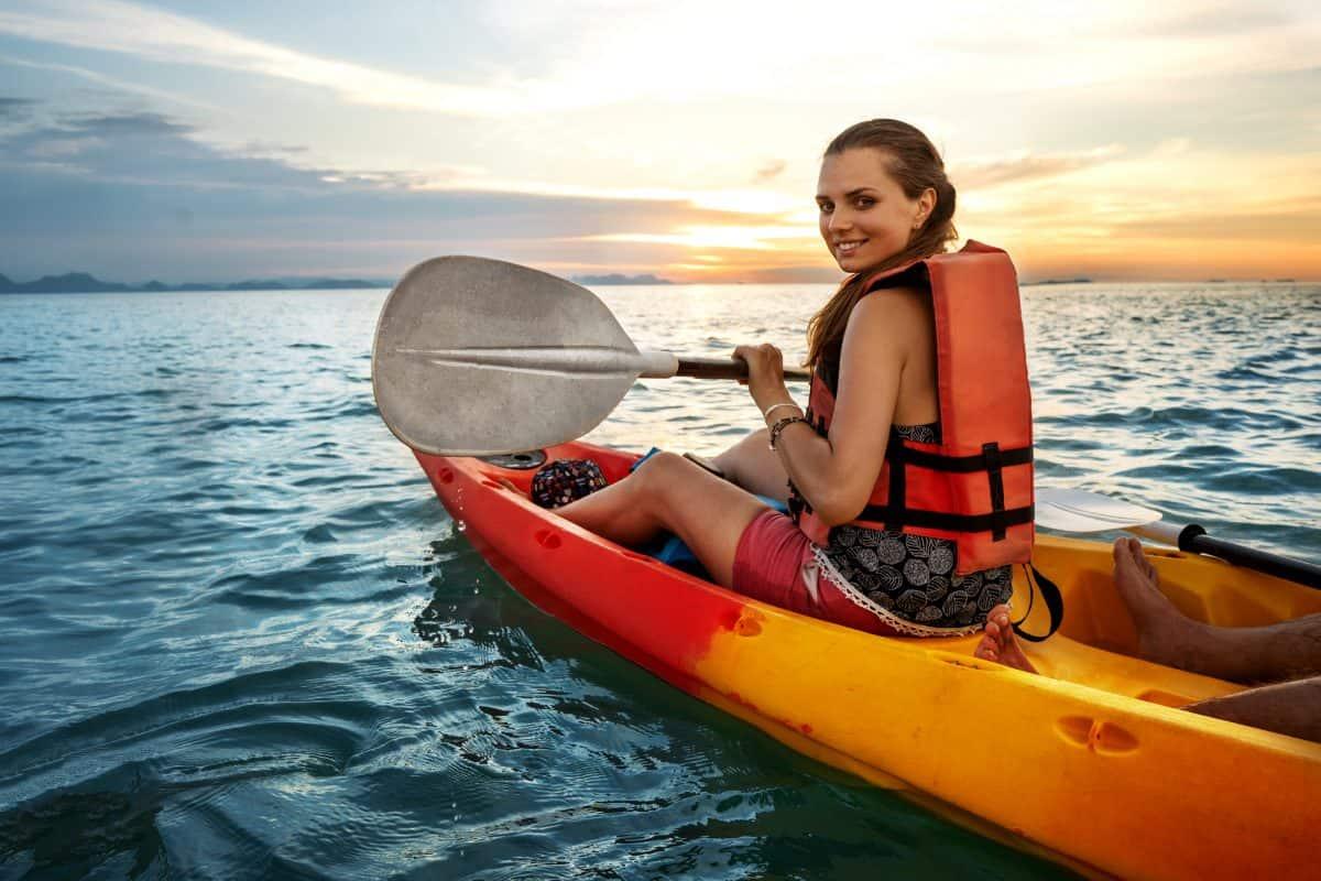 Kayak While Pregnant -  Couple kayaking together. Beautiful young couple kayaking on lake together and smiling at sunset
