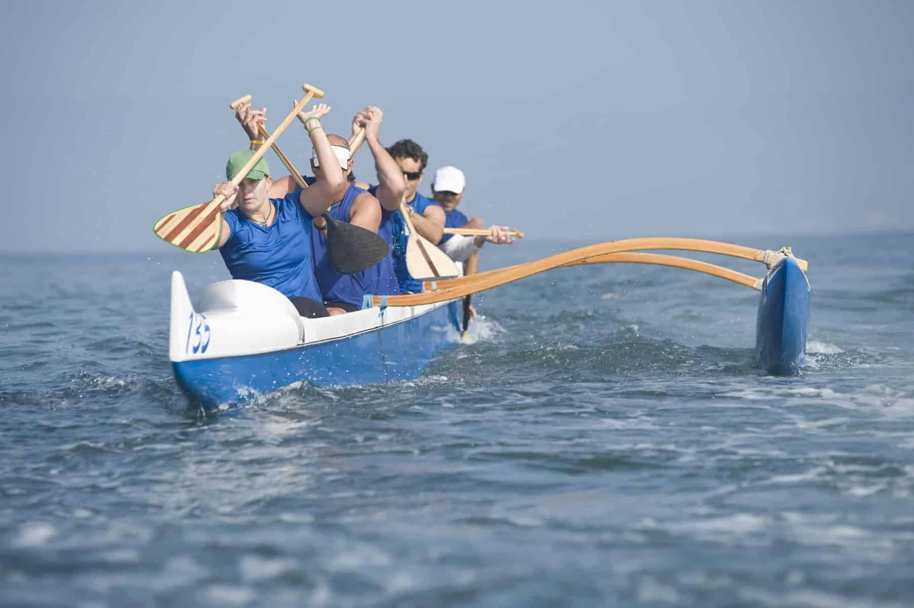 Kayaker in race canoe with outriggers and stabilizers