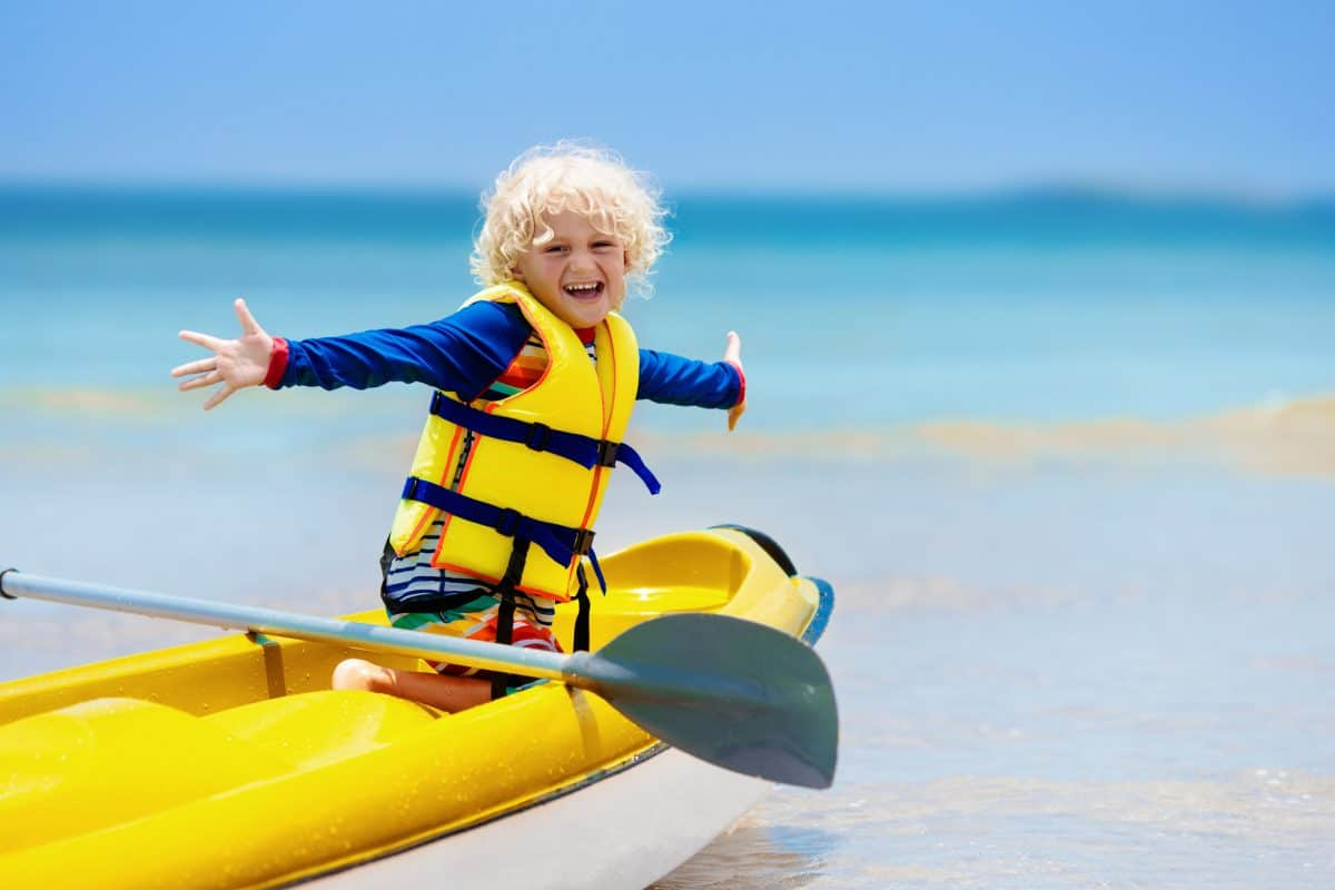 Kids kayaking in ocean. Children in kayak in tropical sea. Active vacation with young kid. Little boy in canoe on beautiful beach. Holiday activity with preschool child. Family water fun.