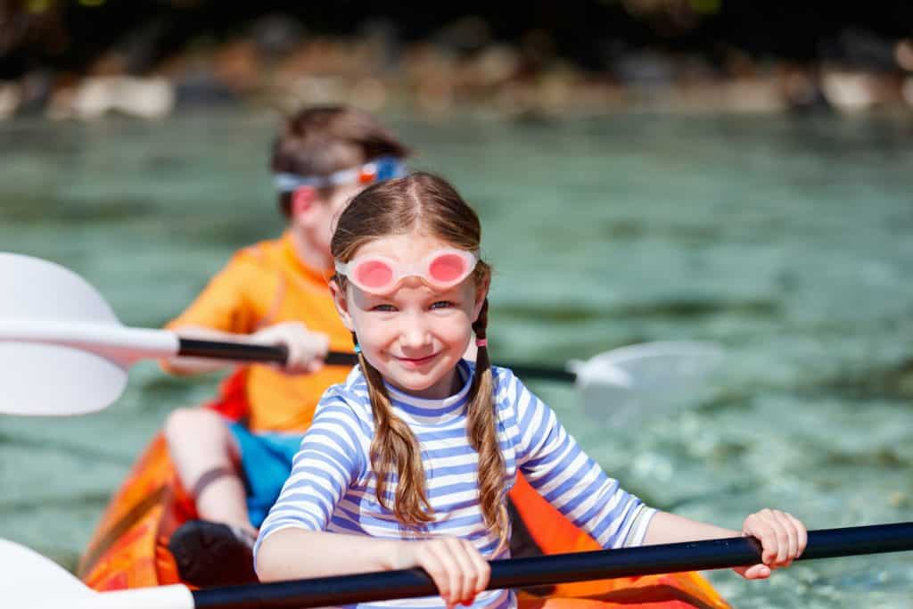 two young kids kayaking wearing swimming goggles
