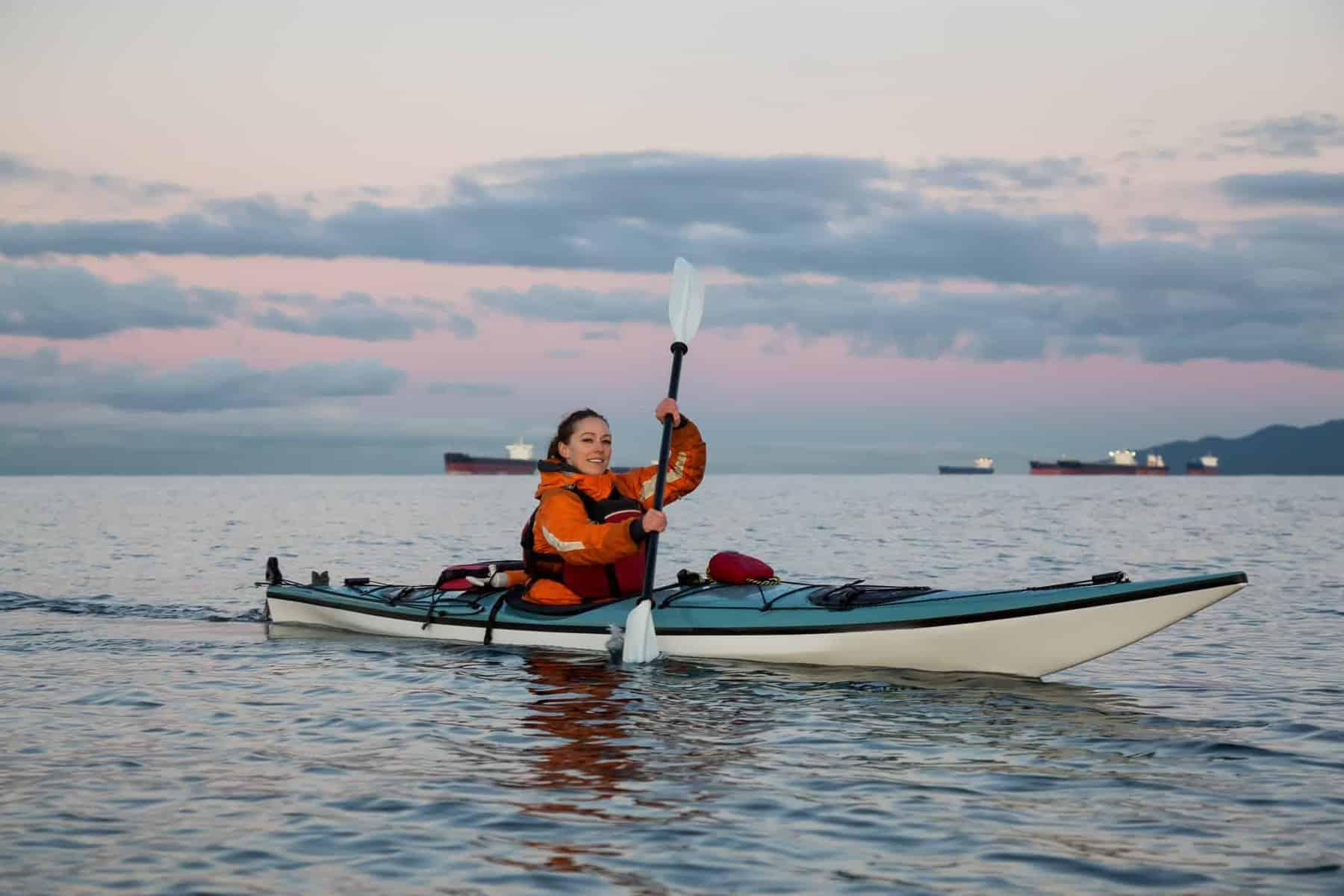 woman paddling  blue sea kayak with kayak rudder