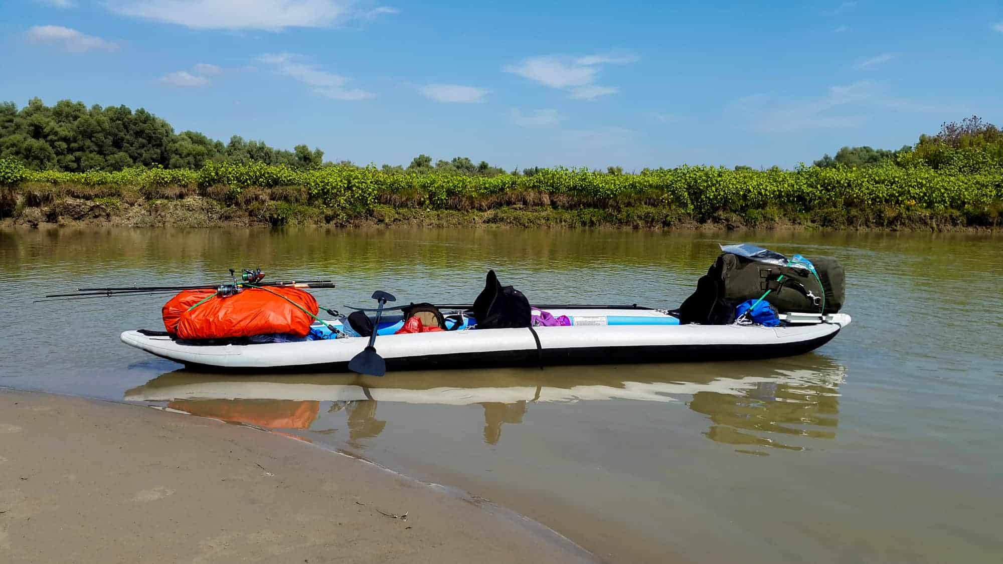 A double person inflatable kayak equipped for touring in a sunny summer