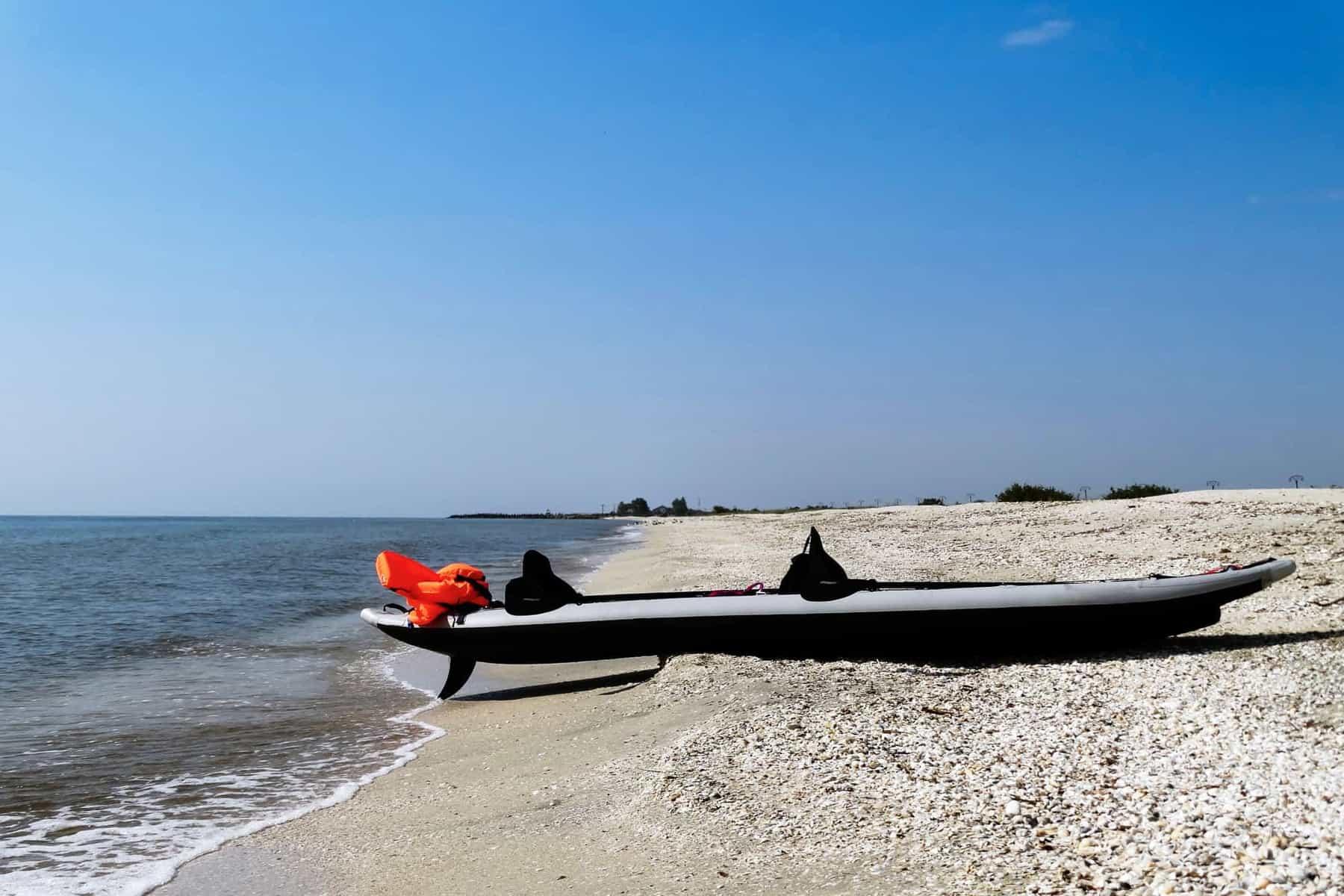 inflatable kayak on a sea shore with kayak skeg