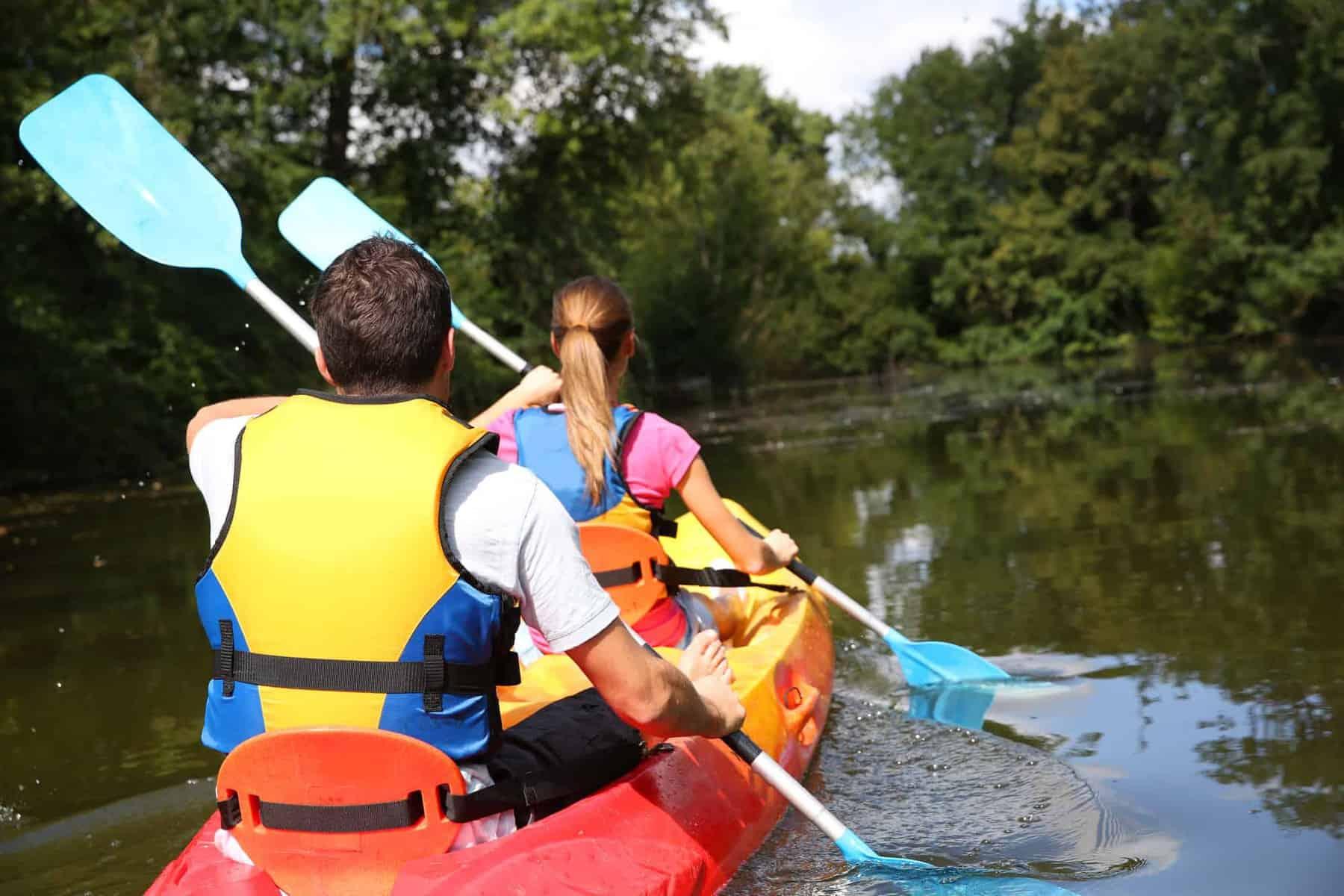 Couple paddling kayak in river