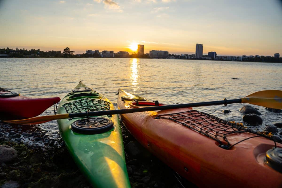 kayak in front of a sunset, kayaks with the skyline of Helsinki in the background, sunset behind Espoo laguuni, golden hour sunset,