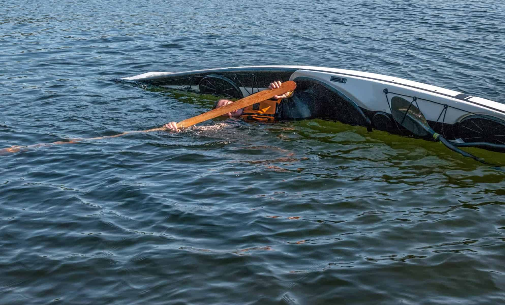 man rolling with a kayak on a lake