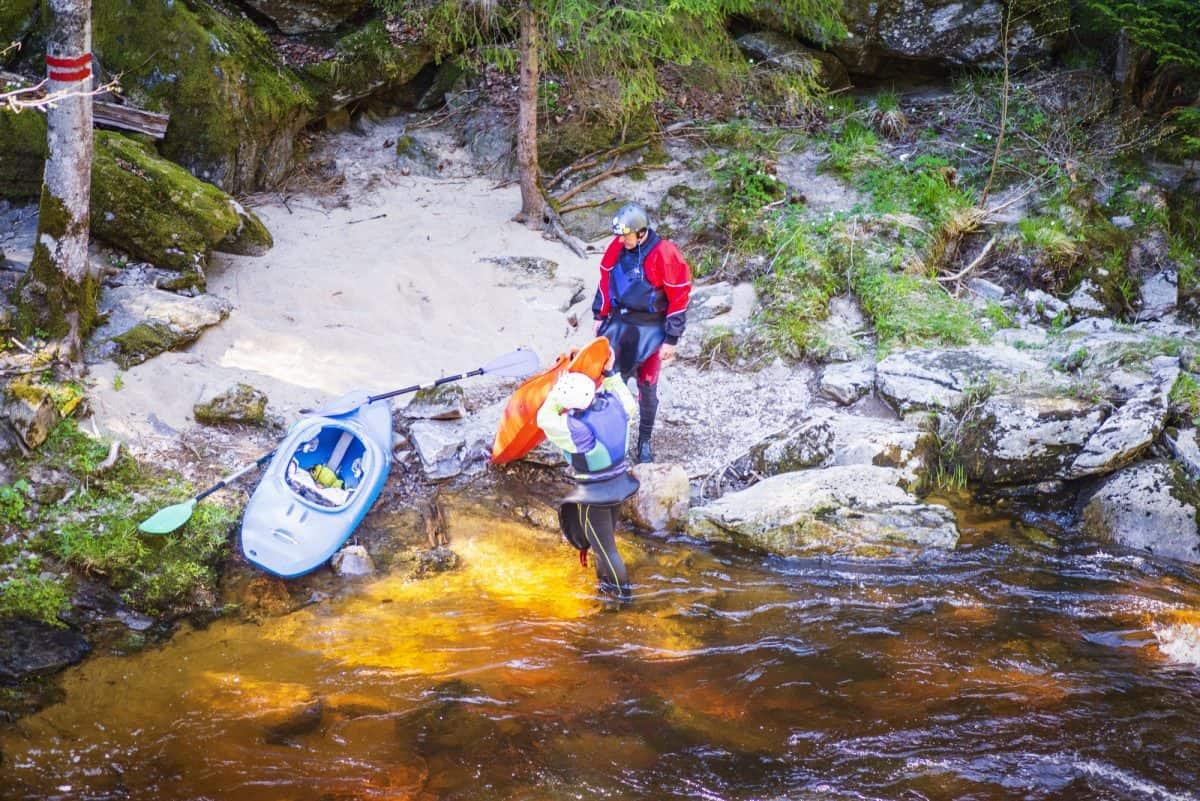2 Kayakers Portaging A Kayak as the river bank