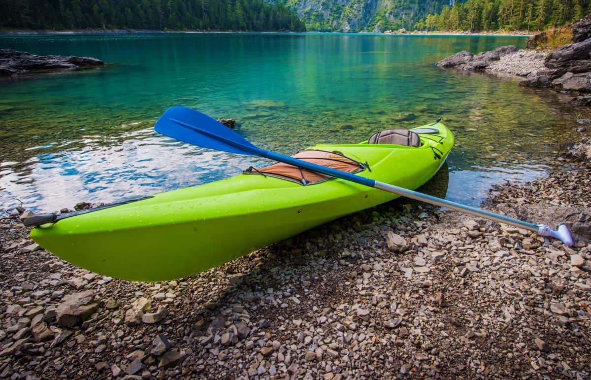 green hardshell kayaks on river bank