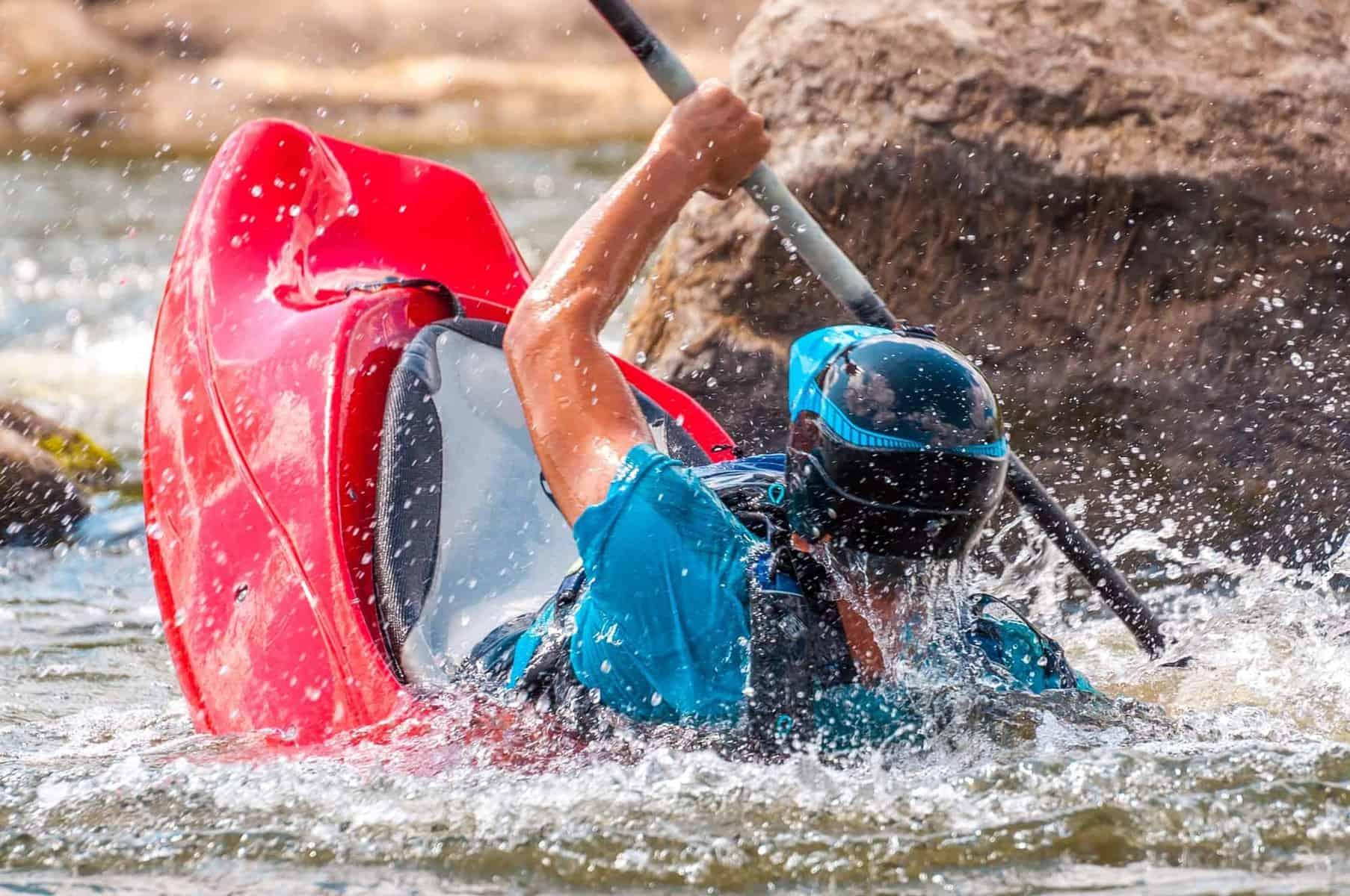 whitewater kayaker rolling a kayak