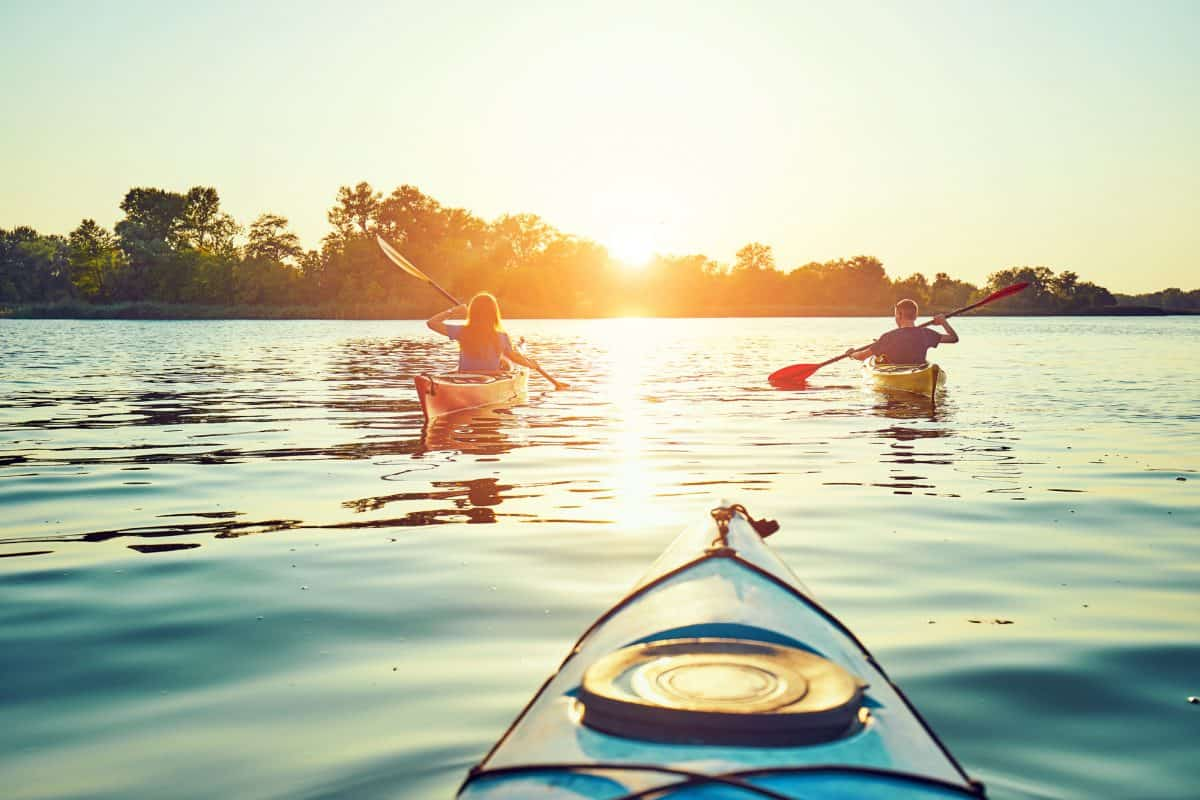 group paddling at sunset in recreational kayak for lakes