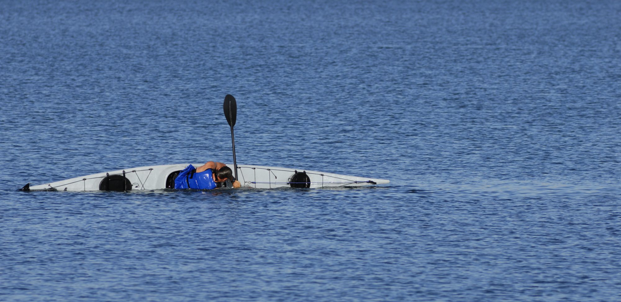 kayaker in open water performing eskimo roll