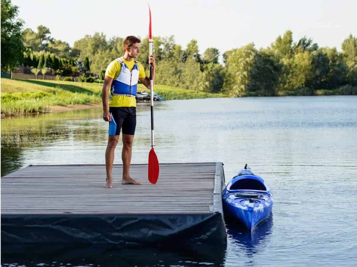 Paddler on pontoon demonstrating how to enter and exit a kayak