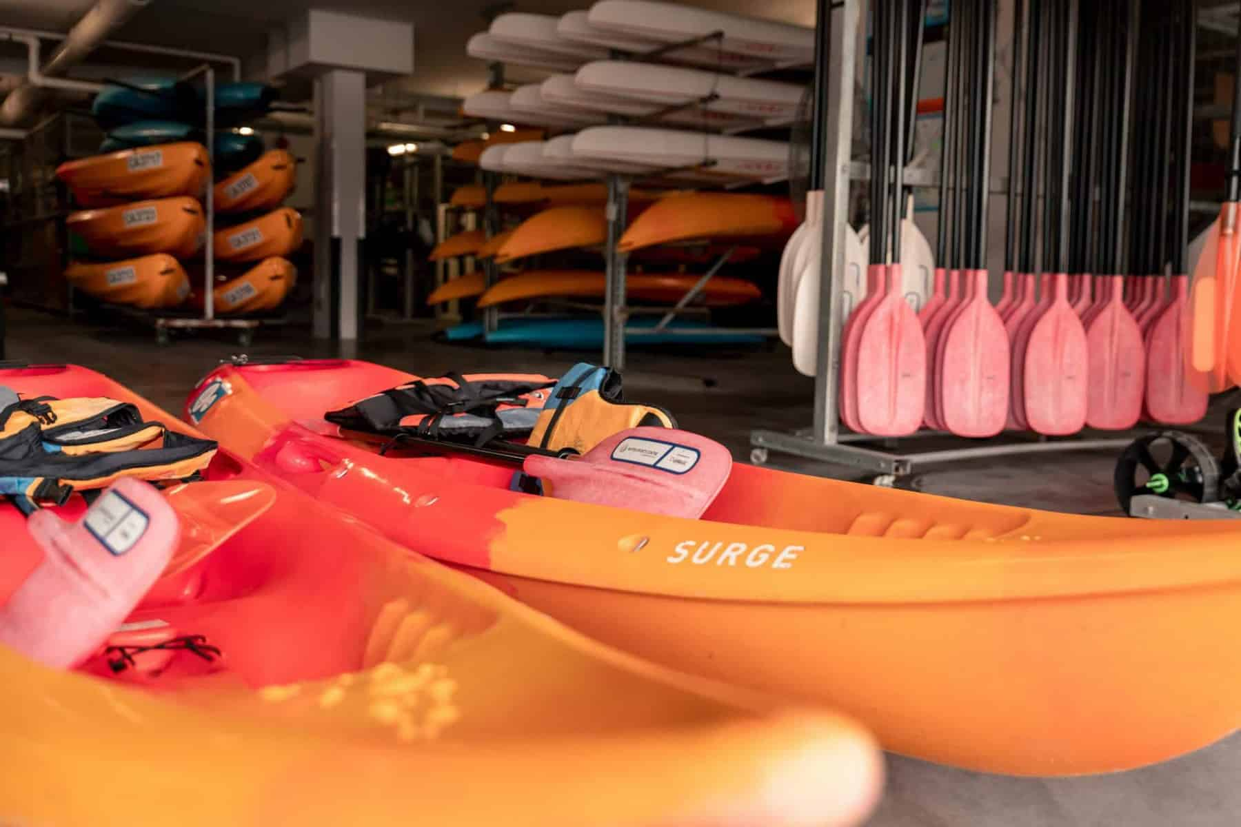 Two Orange Sit On Kayak in storage shed