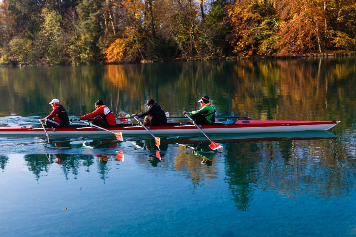 oar vs paddle - 4 rowers on calm winter river