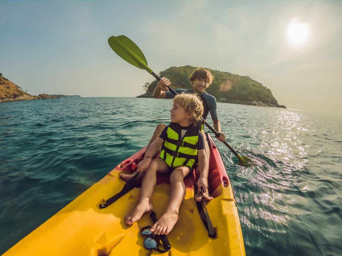 father and son kayaking as a family