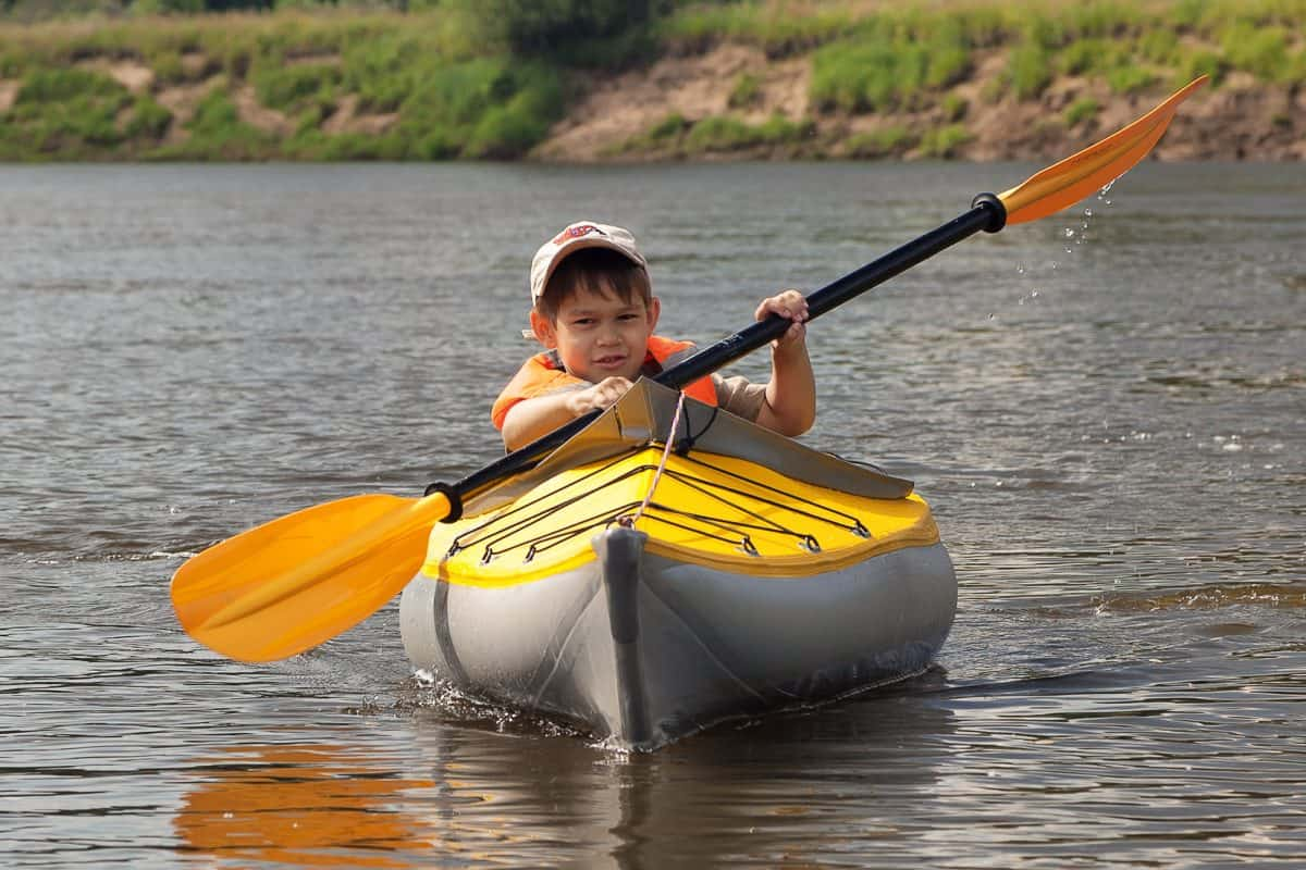 young child solo kayaking in kids kayaks
