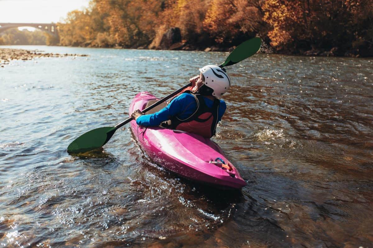 women in white helmet upstream kayaking in pink river boat