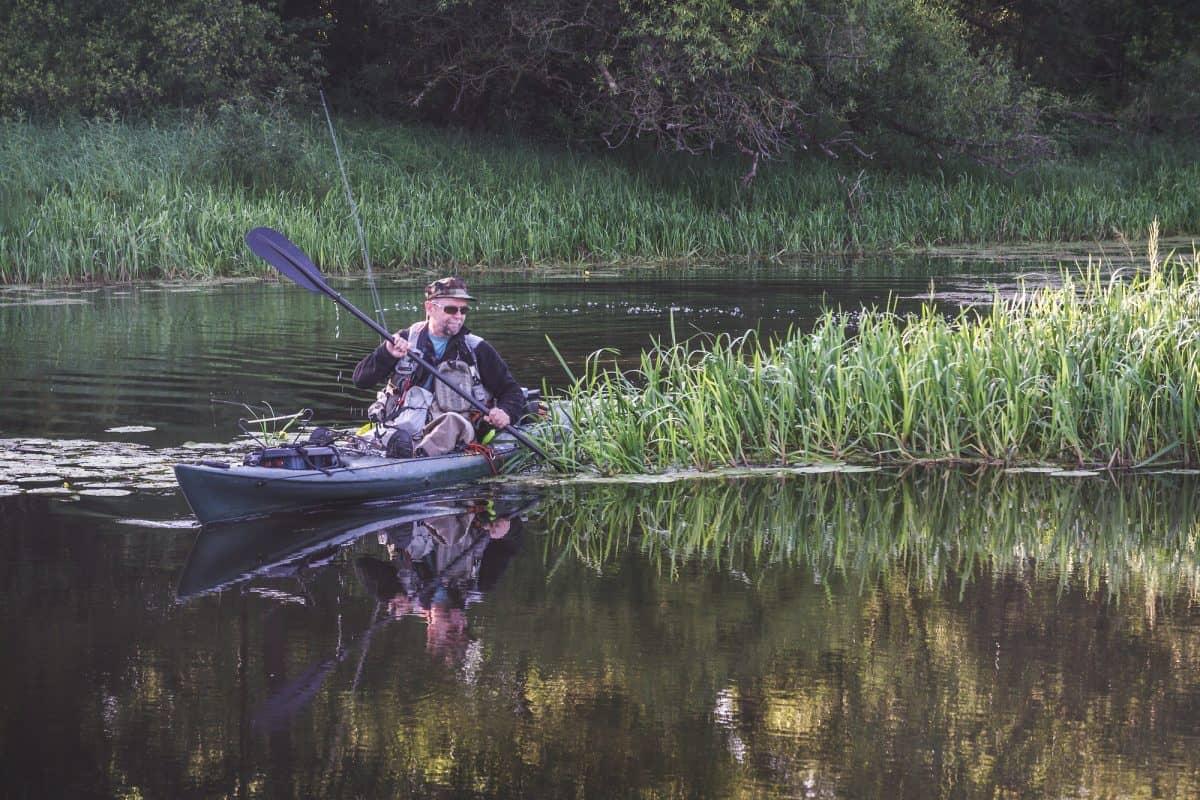 angler paddling around reeds in best cheap kayak for fishing