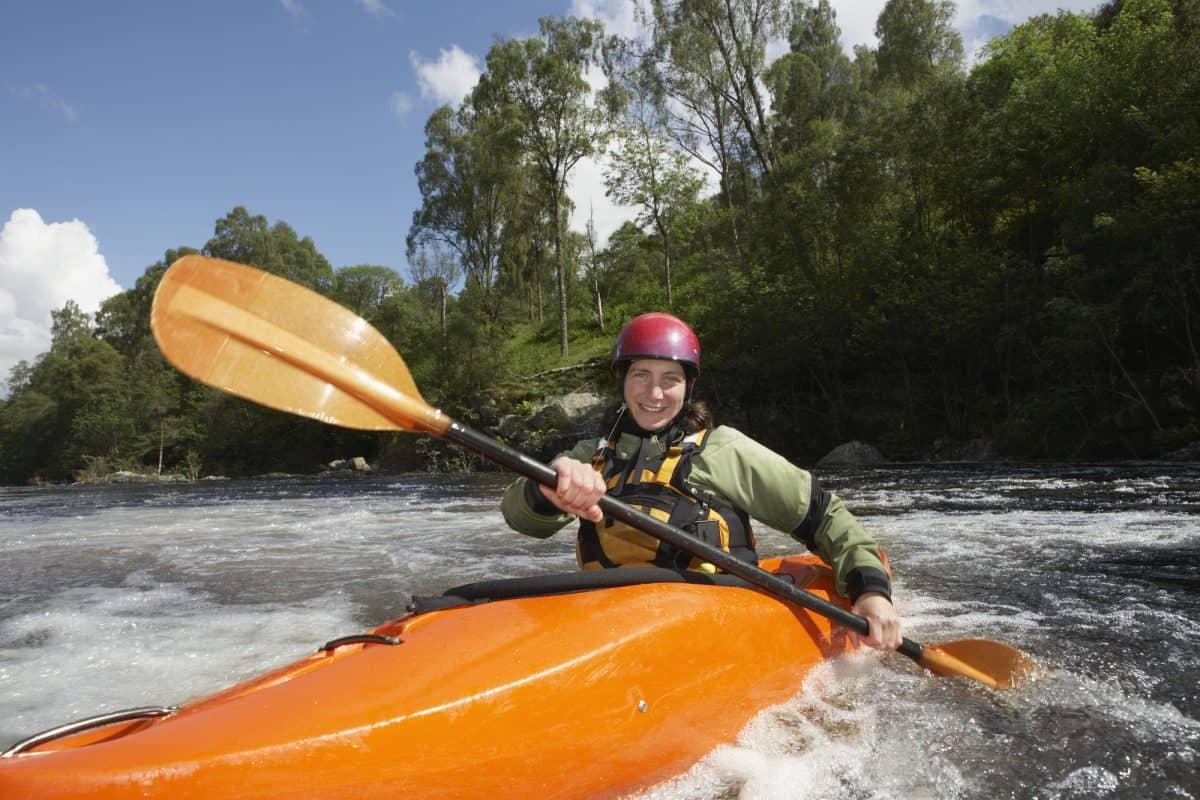 women in red helmet upstream paddling in a orange kayak