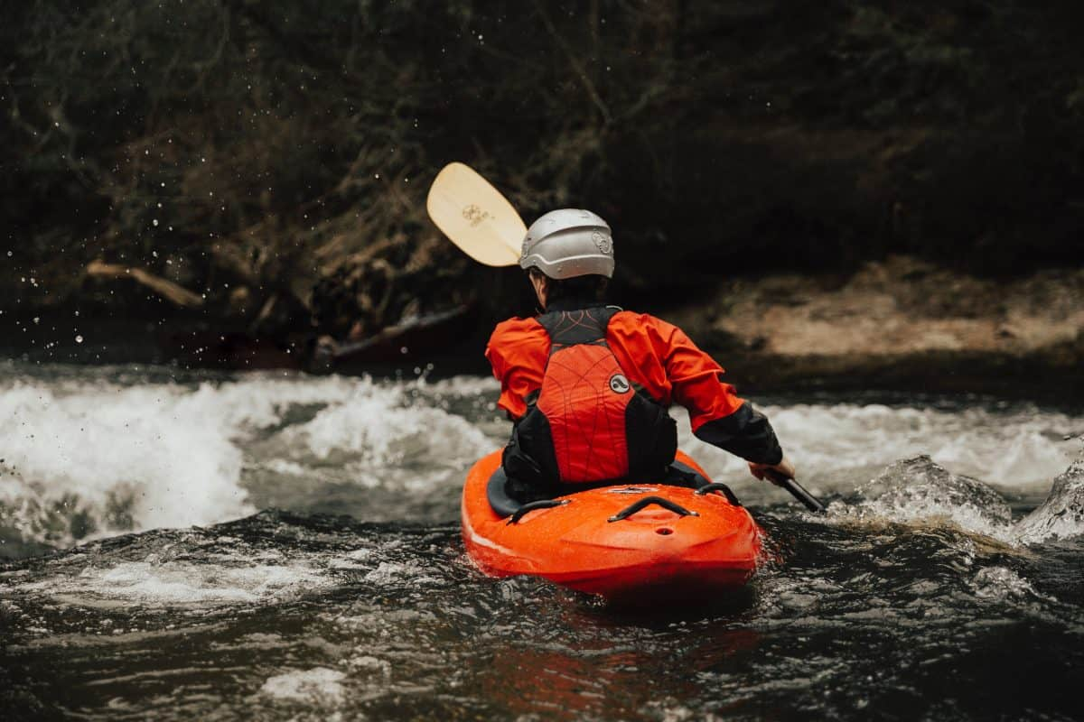 kayaker paddles best kayak for river into oncoming rapids