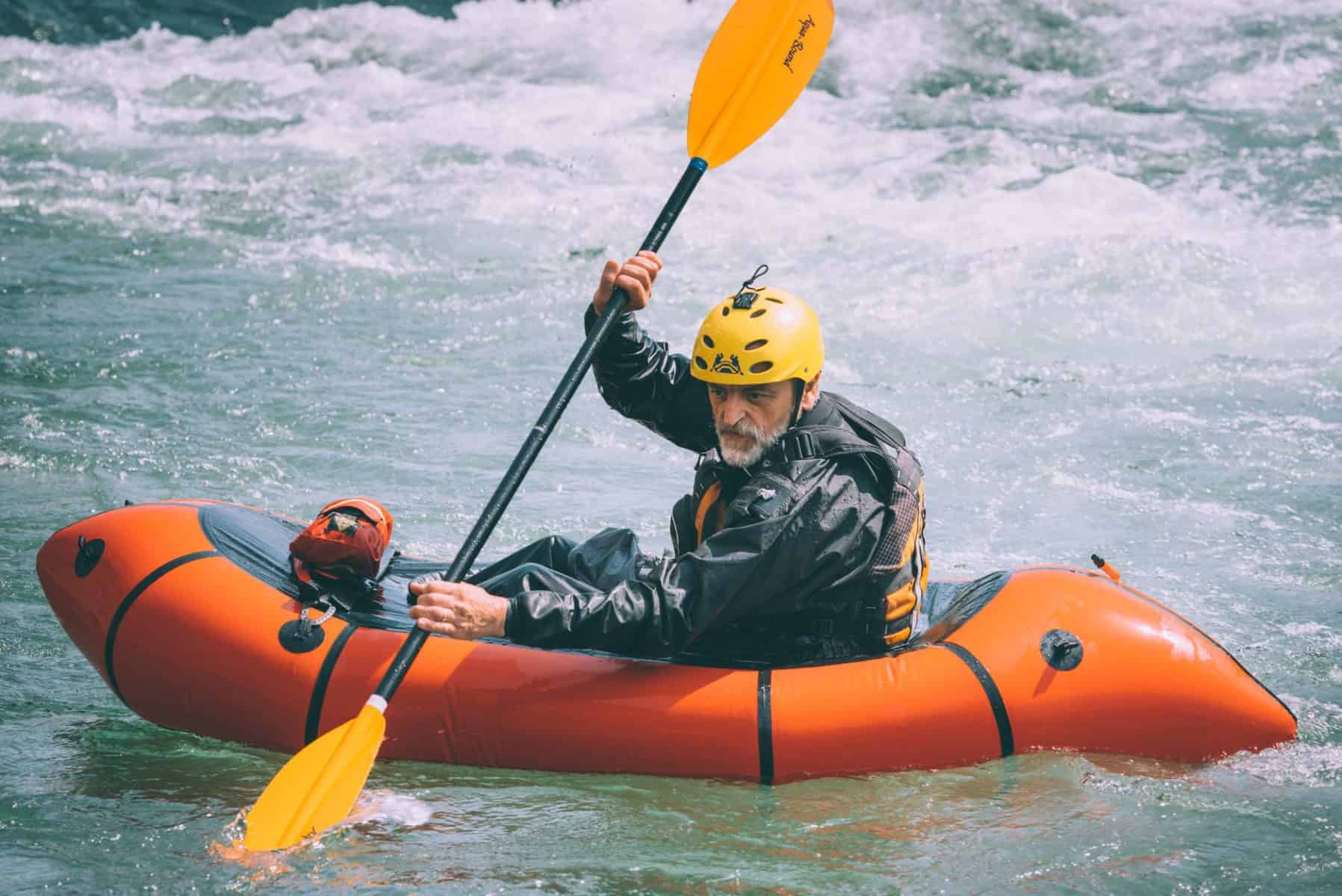 Man paddle orange whitewater kayak in drysuit