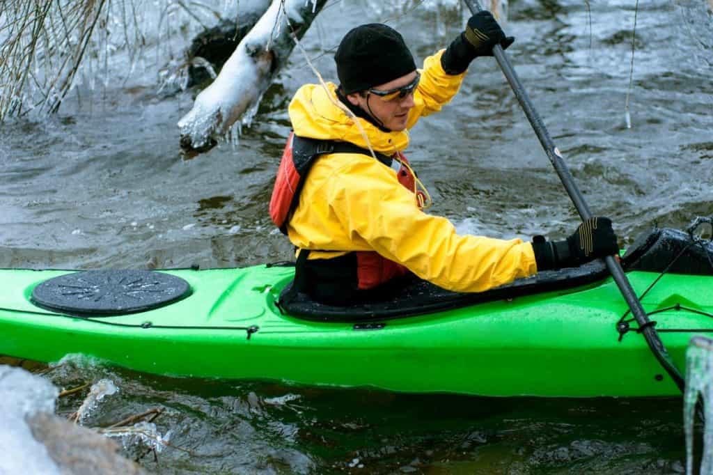Man in yellow kayak dry suit paddling green kayak in cold water