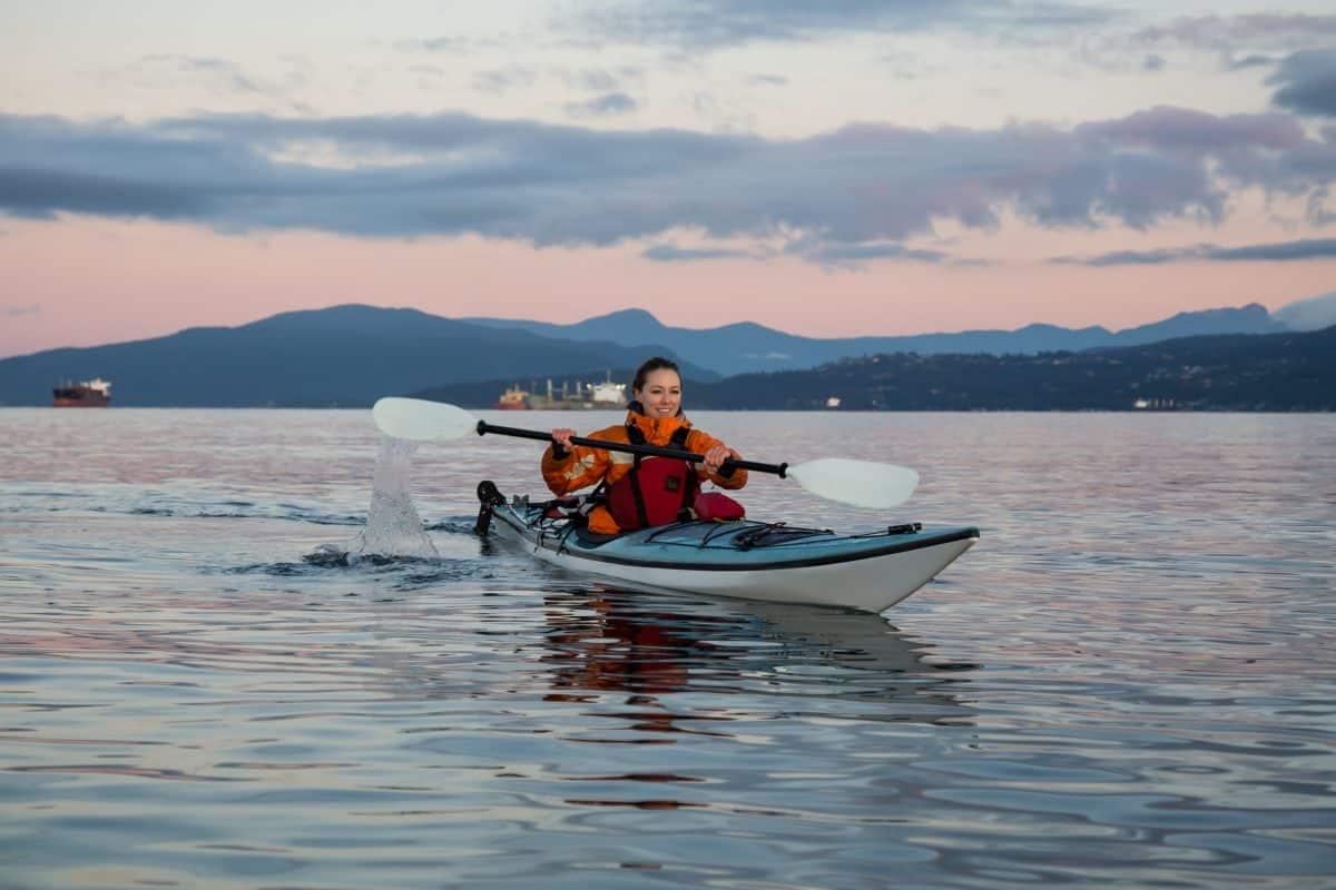 Womwn in rwd drysuit paddling white and blue kayak