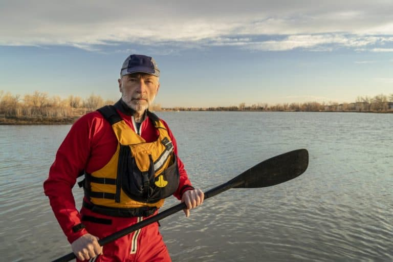 Man in red drysuit and yellow pfd holding kayak paddle
