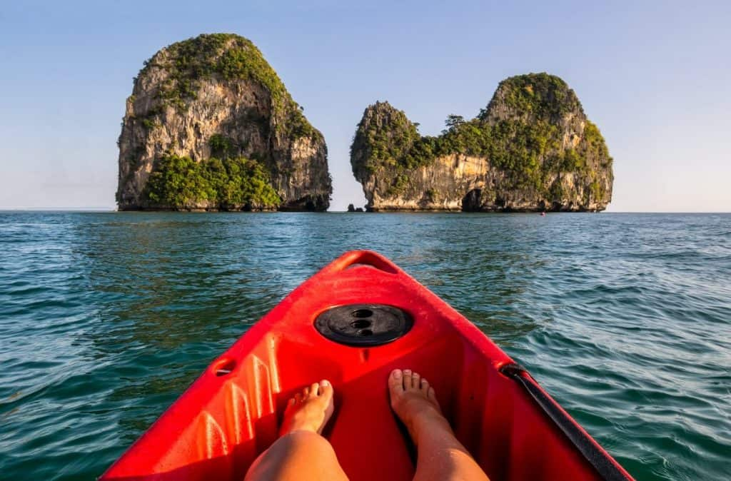 People of front of kayak in ocean of thailand, looking at to limestone rock
