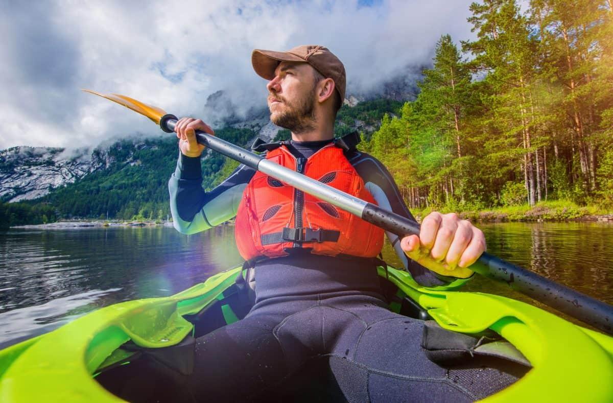 Man paddling kayak wearing full wetsuit vs drysuitsuit