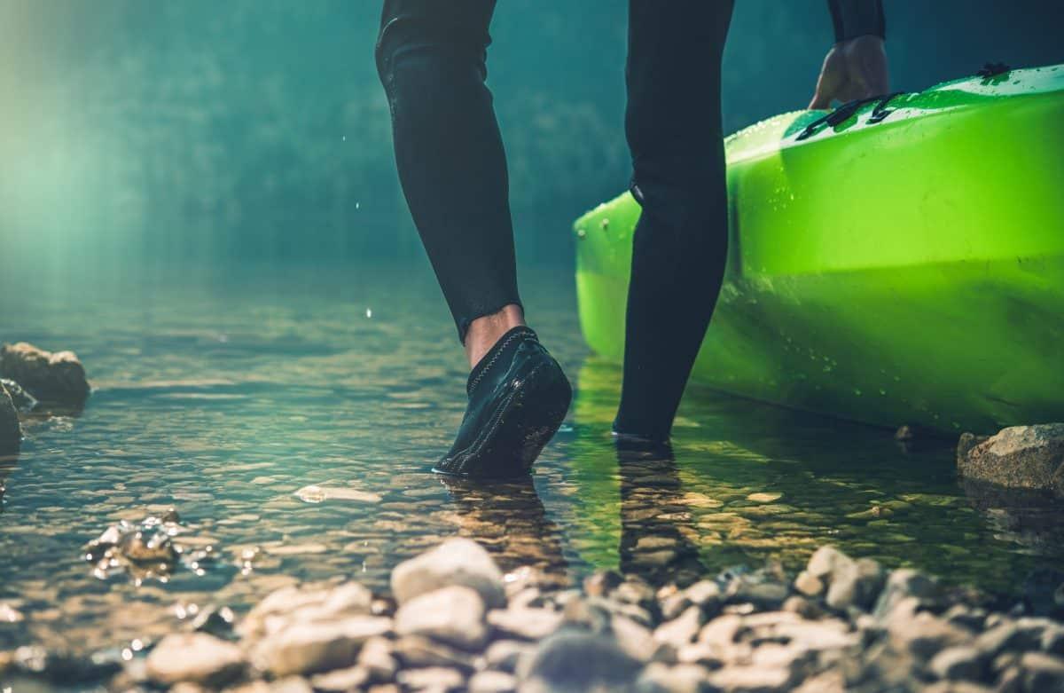 Man wearing kayaking shoes pushing green kayak into water
