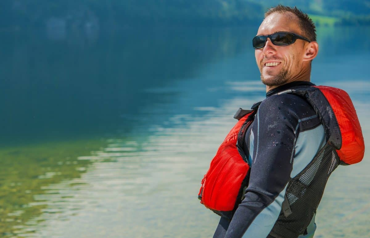 Man in kayak wetuit and red PFD