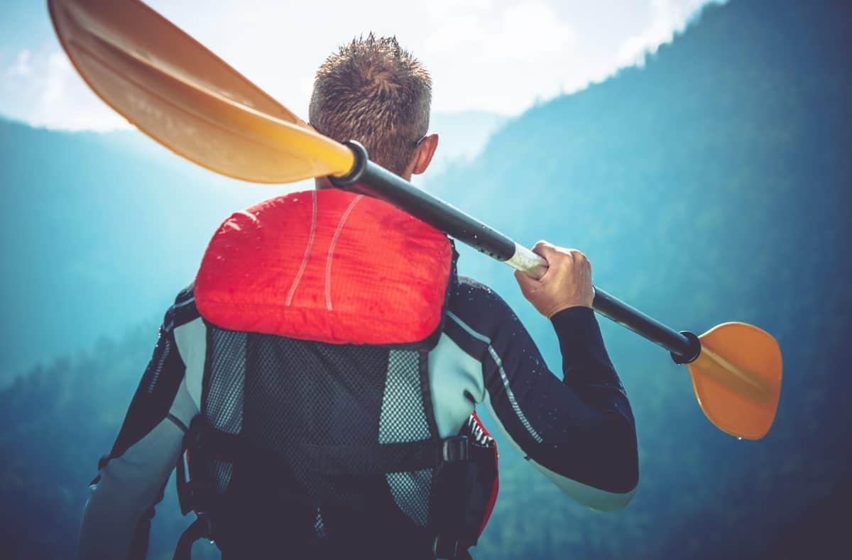 Man in kaya wetsuit holding paddle