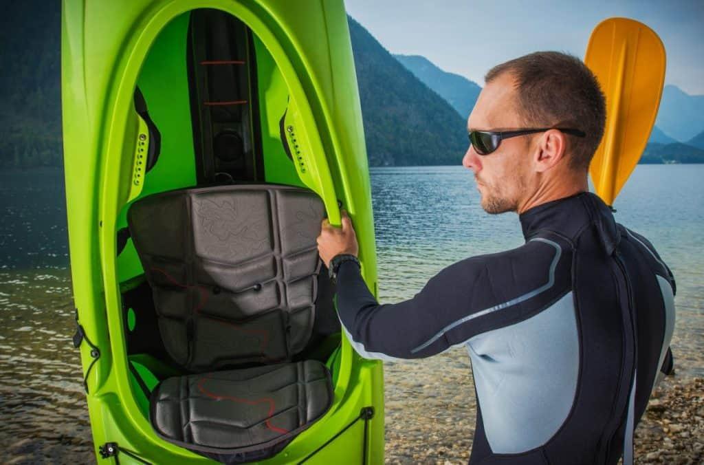 Man holding green kayak wearing black wetsuit
