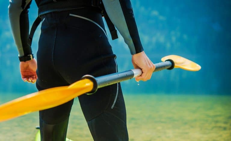 Man In wetsuit holding kayak paddle