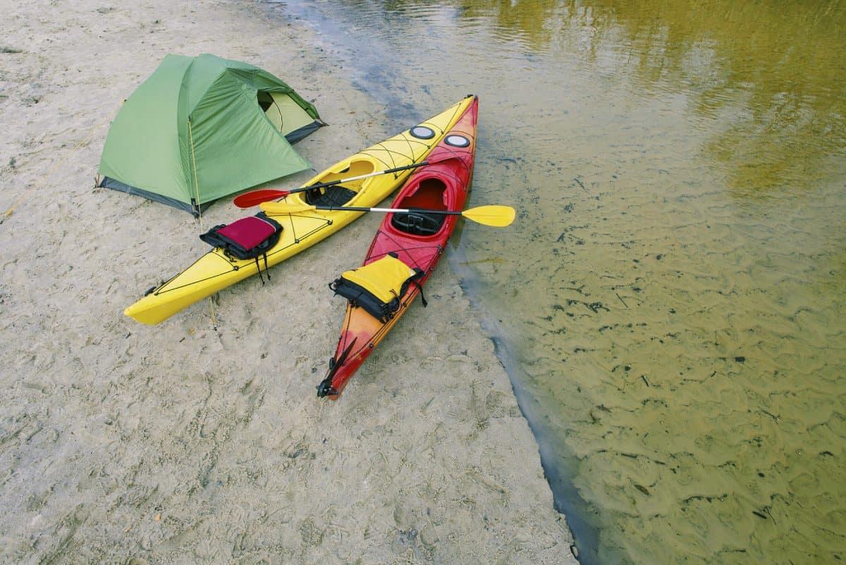 Touring kayak on bank with tent