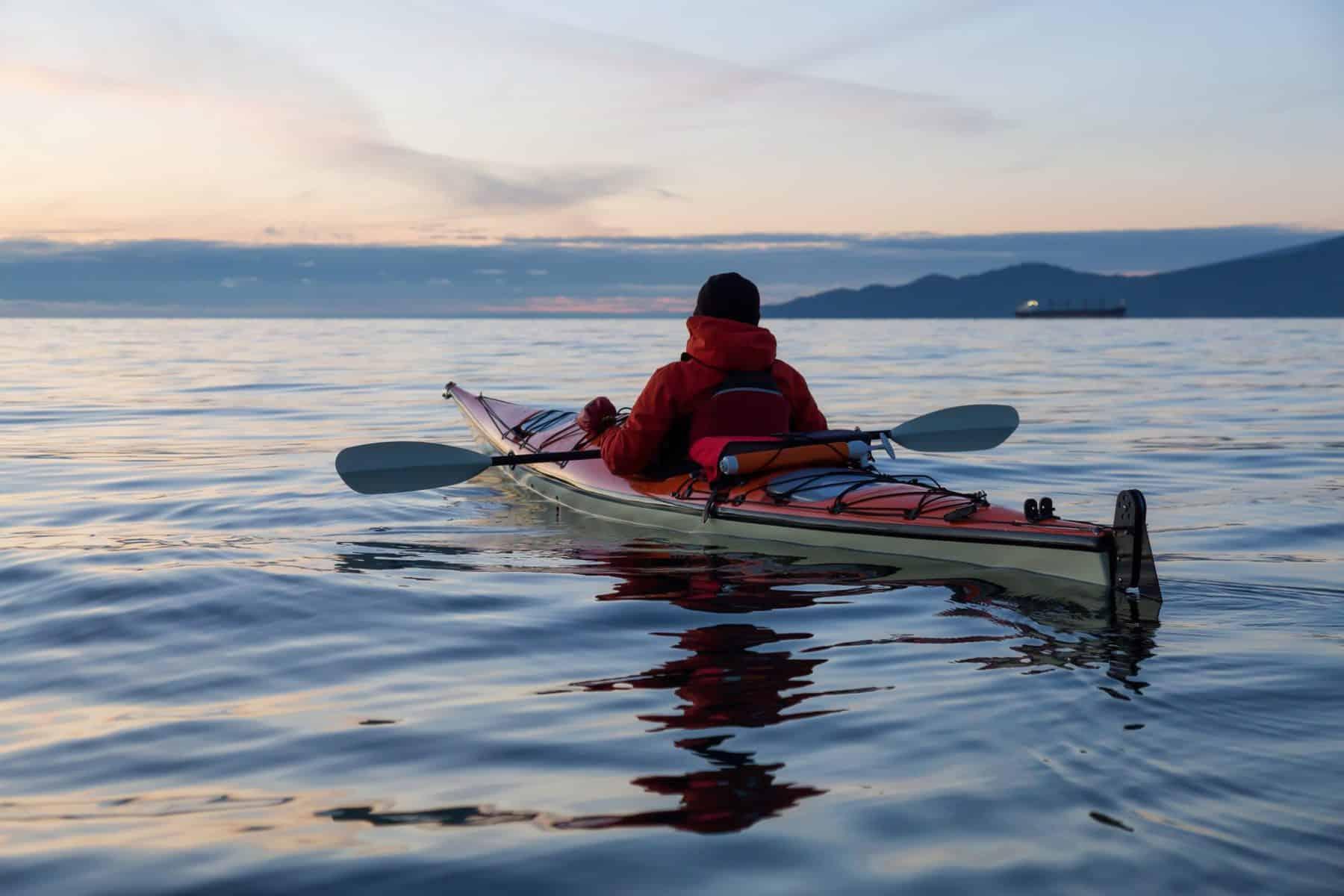 Man in touring kayak in open sea