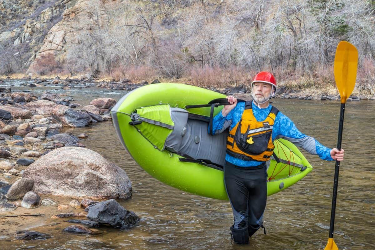 Man wearing a kayaking shoes carries kayak on shoulder