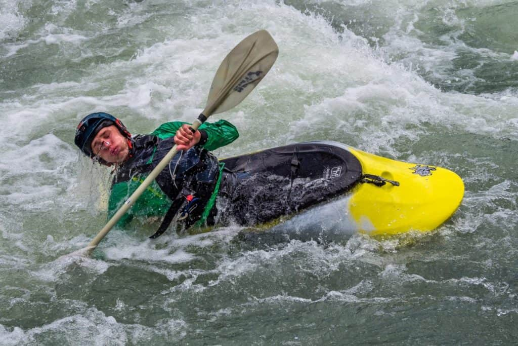 Man in yellow whitewater kayak, wearing green dry suit, rolling in rapids
